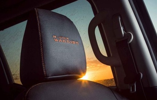 N-Trek Warrior Headrest Signature embroidered front head rest, is matched to partial leather seats with dark orange fabric seat inserts.